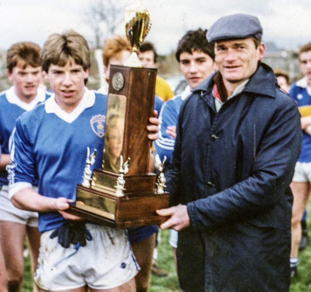 Tony O Keeffe (Secretary Co. Board) presents the U-17 Trophy to Timmy Fleming (Capt.)