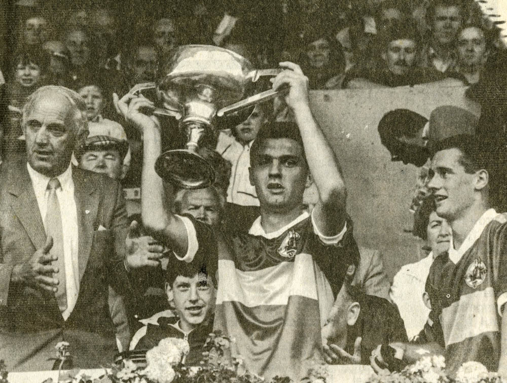Danny Cahill (capt.) receives the Munster Minor Football Trophy from Michael Maher, Vice-Chairman Munster Council, while Billy O Sullivan looks on.
