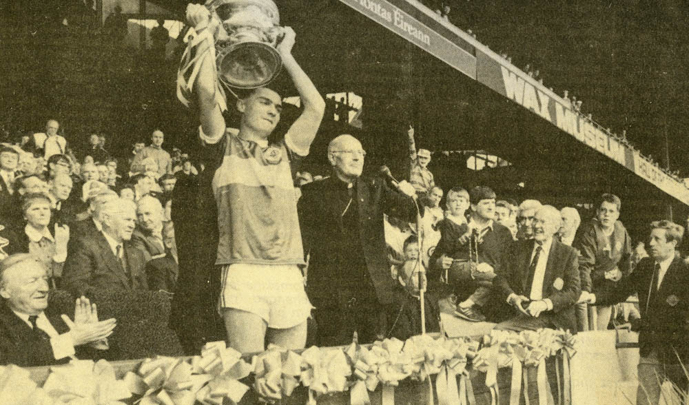 Danny Cahill, Kerry Minor Football Captain, proudly holds the Tom Markham Cup aloft.